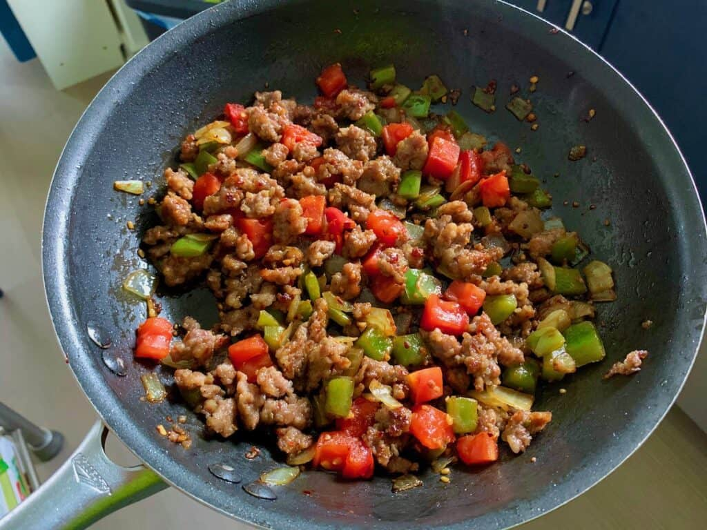sausage peppers tomatoes and onions in a frying pan