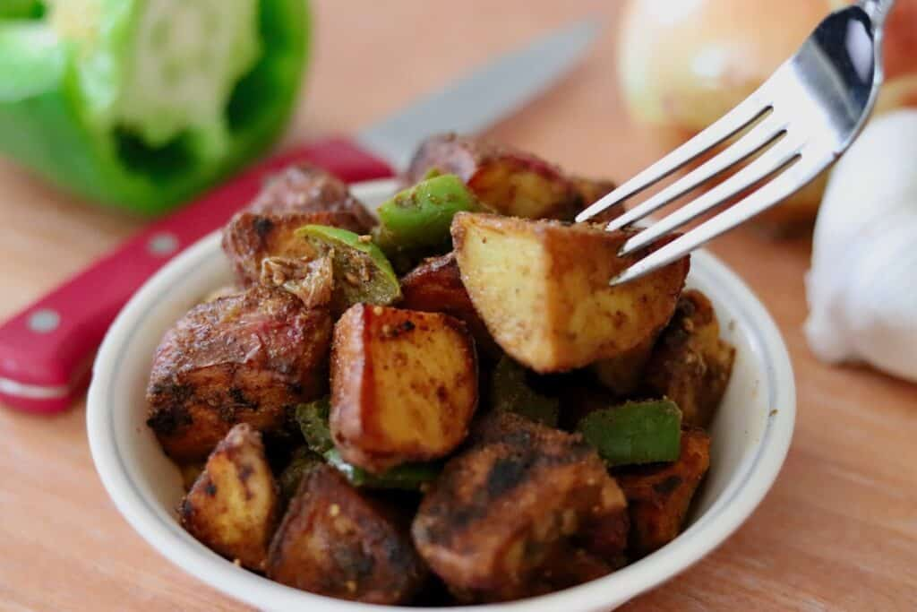 fork with bowl of indian spiced breakfast potatoes