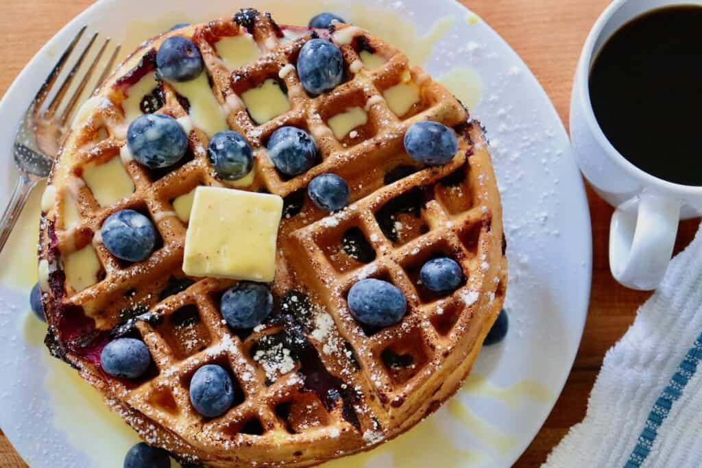 Top view of a stack of blueberry waffles with Meyer Lemon Curd Créme Anglaise