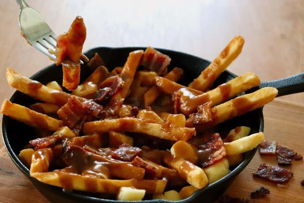 Fork digging into smokey maple bacon poutine