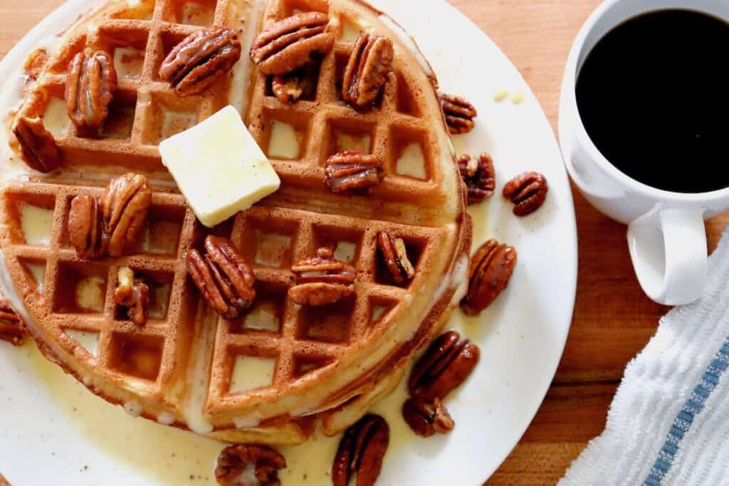 Pecan waffles on table with cinnamon créme anglaise sauce and cup of coffee