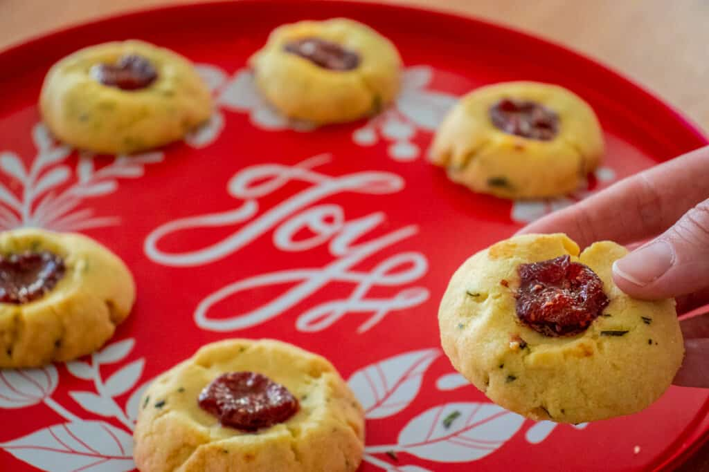 Rosemary thumbprint cookies on a tray and one is in a hand