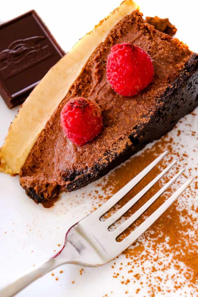 Slice of double espresso chocolate cheesecake with raspberries