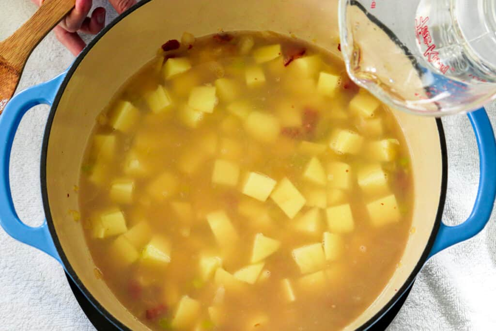 Adding water to the potatoes to make clam chowder