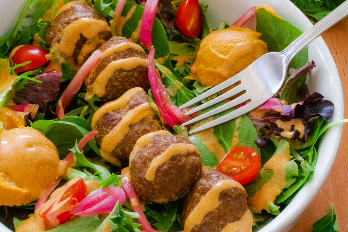 Spicy meatballs with harissa dressing over a salad