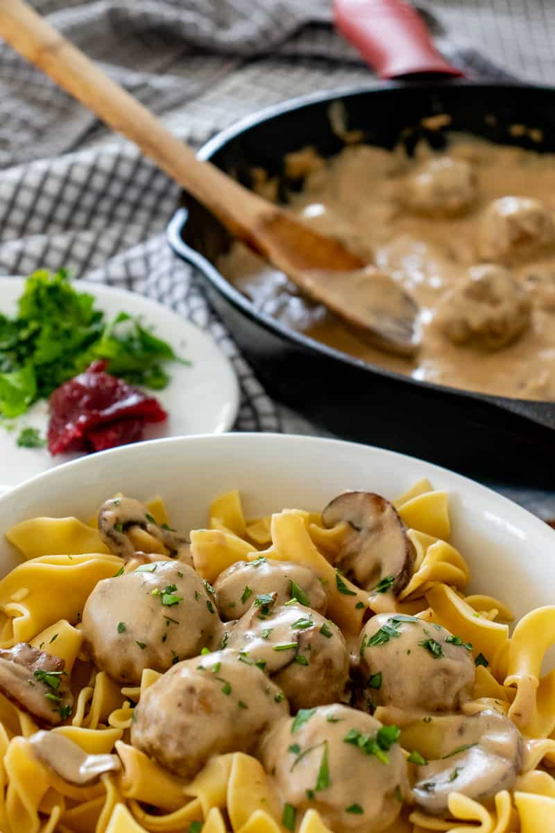 Swedish meatballs and noodles with cast iron skillet in background