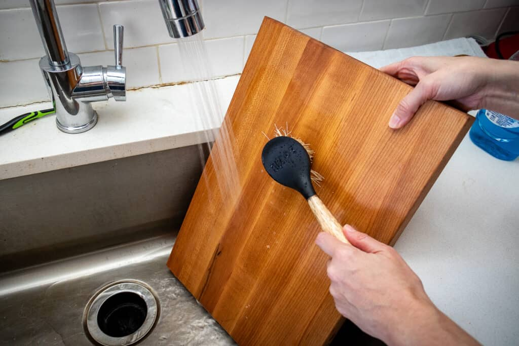 Rinsing a cutting board with soap and water