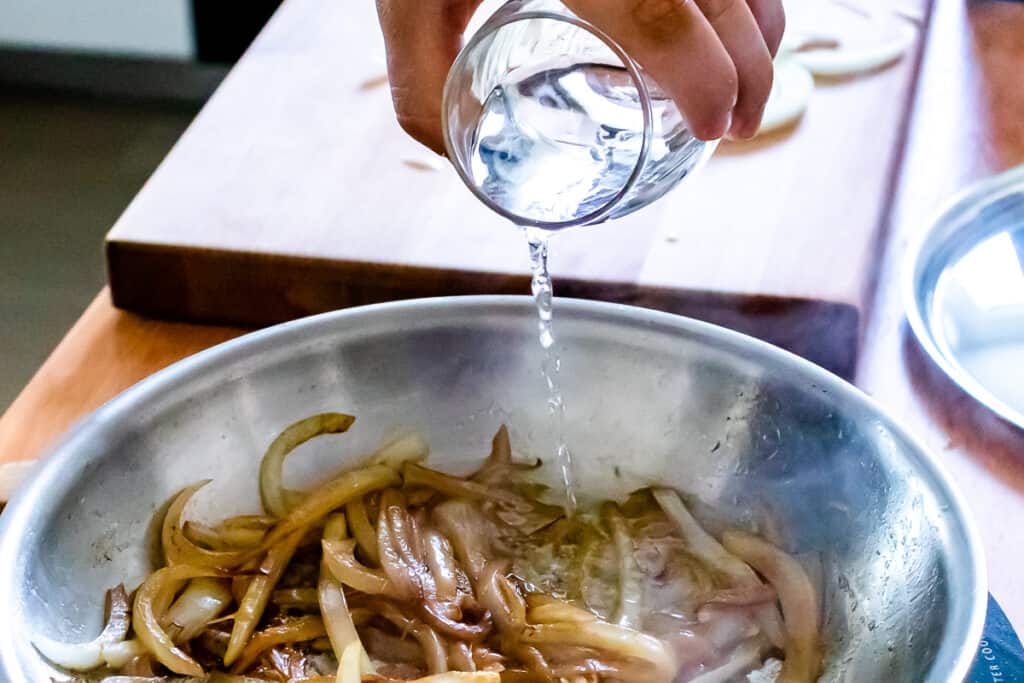 Deglazing the pan to caramelize onions